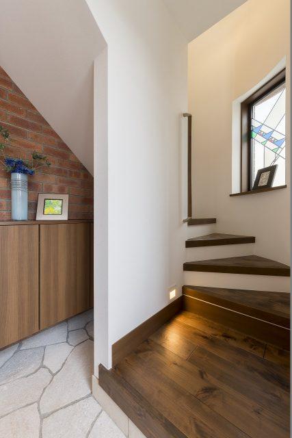 二階への階段は、やわらかな曲線が特徴的です。ステンドグラスからの光もアクセントに。