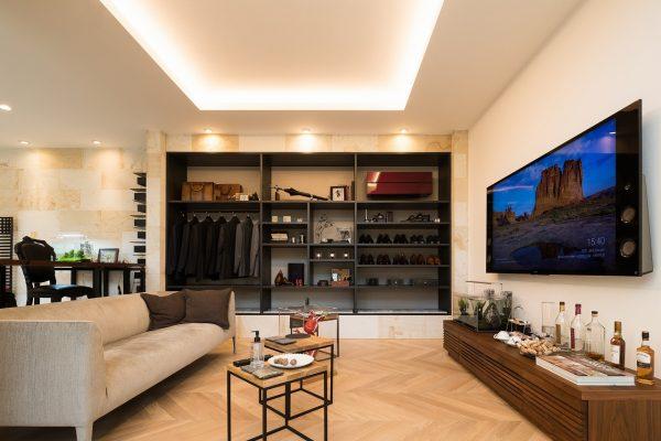 一段下がったリビング。大きな壁掛けのテレビとブティックのような魅せる収納