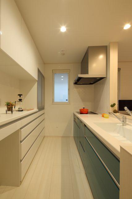 アクセントとなる、ターコイズ色のキッチン。背面の収納棚は、壁紙と合わせて白でコーディネート。